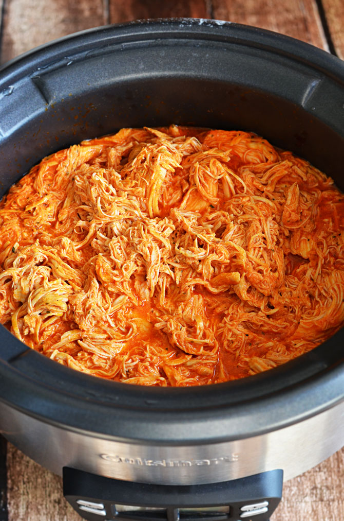 Simple Slow Cooker Shredded Buffalo Chicken.  This recipe is a must-have for the Super Bowl and is so easy to make!  Only 4 ingredients necessary, and it's way healthier than fried wings (although it tastes just as delicious!)! | hostthetoast.com