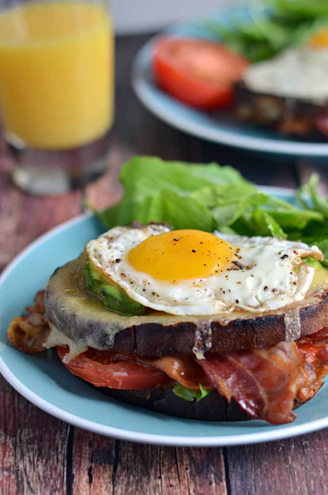 B.L.A.T Croque Madames.  Crispy bacon, fresh tomato and arugula, smoky cheddar cheese, creamy avocado, and a perfectly fried egg.  Does it get any better than that?  The answer is no, it does not. | hostthetoast.com