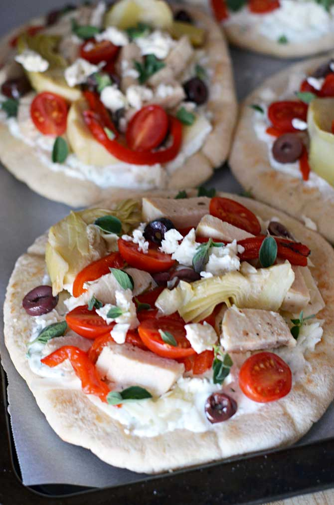 """Loaded Greek Chicken """"Pitzas"""".  These pita bread pizzas are topped with tzatziki, chicken breast, 3 cheeses, artichokes, olives, roasted red peppers, and tomatoes.  They're so easy to make and they taste amazing!  The leftovers even taste great cold! 