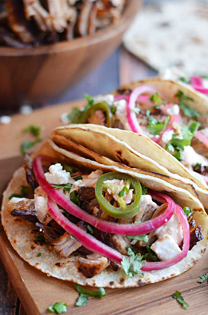 Crock Pot Carnitas Tacos.  Super crispy and juicy with no added lard!  Way easier to make in the crock pot and delicious with quick pickled onions, jalapenos, and chipotle cream.   My boyfriend is crazy about them!  | hostthetoast.com