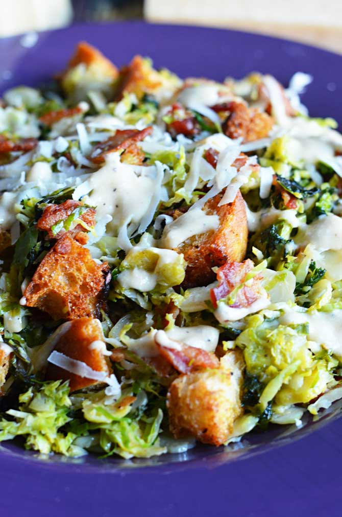 Warm Brussels Sprouts and Kale Bacon Caesar Salad.  The sprouts and kale are sauteed in the bacon drippings and then tossed with creamy Caesar dressing, homemade croutons, and plenty of freshly grated parmesan cheese.  I want to eat this every day. | hostthetoast.com