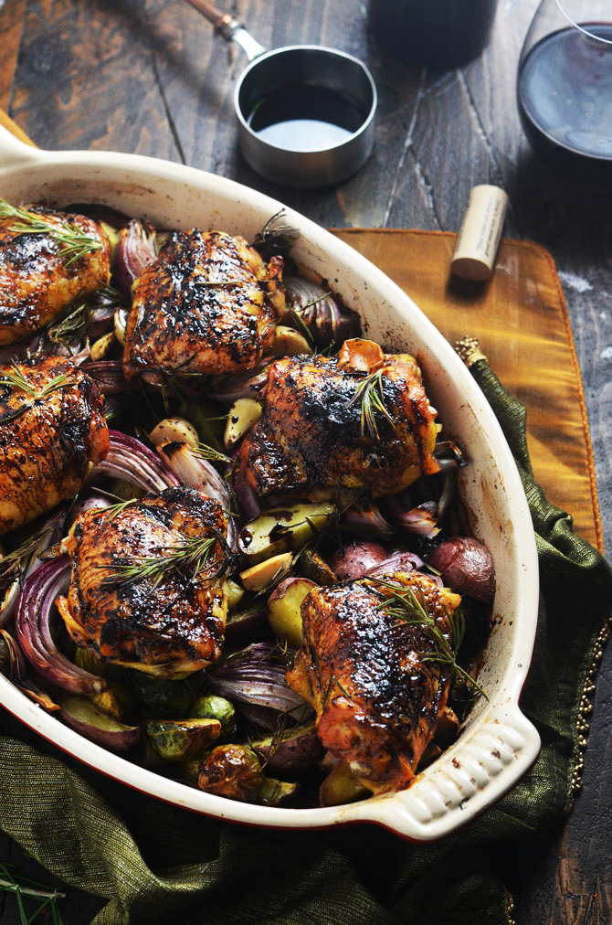 Balsamic-Red Wine Roasted Chicken Thighs and Vegetables. Juicy, crispy-skinned chicken thighs rest over a bed of potatoes, brussels sprouts, whole garlic cloves, and onions. Fresh rosemary and a brush of sweet and vinegary reduction packs in a punch of flavor. | hostthetoast.com