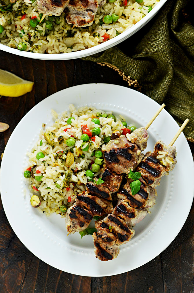 Yogurt Marinated Lamb Skewers with Mint Pistachio Pesto Pilaf. Marinating the lamb in a mixture of yogurt, garlic, lemon, and cumin makes it tender, tangy, and bright. The rice pilaf, with mint-pistachio pesto mixed in, is the perfect pairing for this springtime dinner. | hostthetoast.com