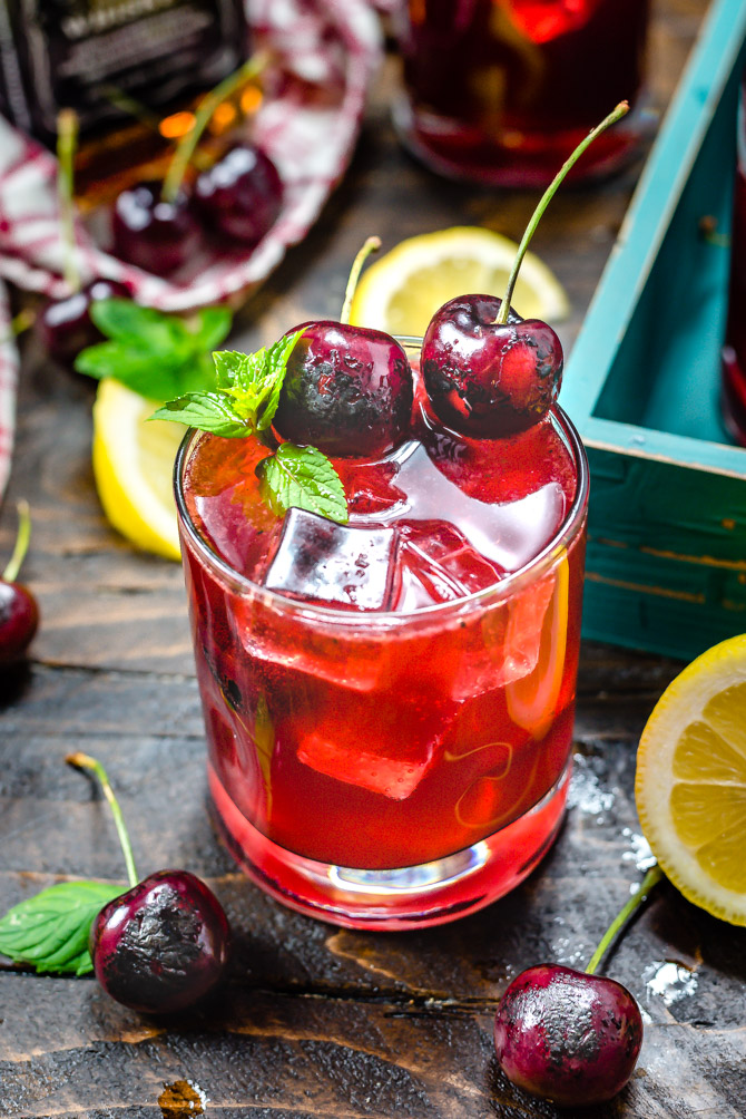 A red Charred Cherry Whiskey Lemonade cocktail in a small glass with mint, ice, and charred cherry garnishes.