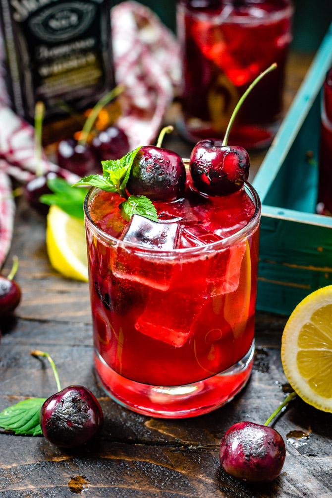 A red Charred Cherry Whiskey Lemonade cocktail with ice in a small glass. Charred cherries and mint garnish the drink, which is sitting on a wooden table.