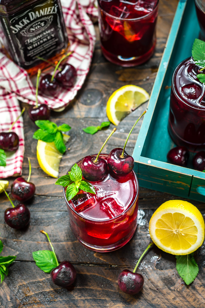 An overhead shot of a tabletop with Charred Cherry Whiskey Lemonade cocktails in small glasses, a Jack Daniels whiskey bottle, fresh mint, charred cherries, and lemon wedges.