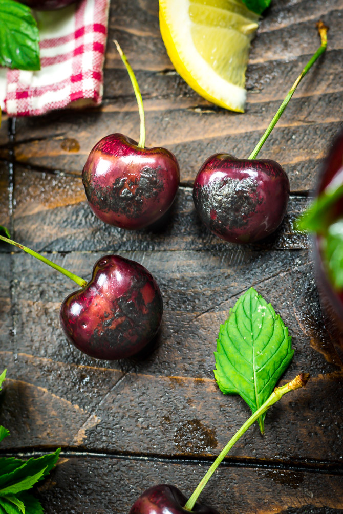 Charred cherries on a brown wooden table.