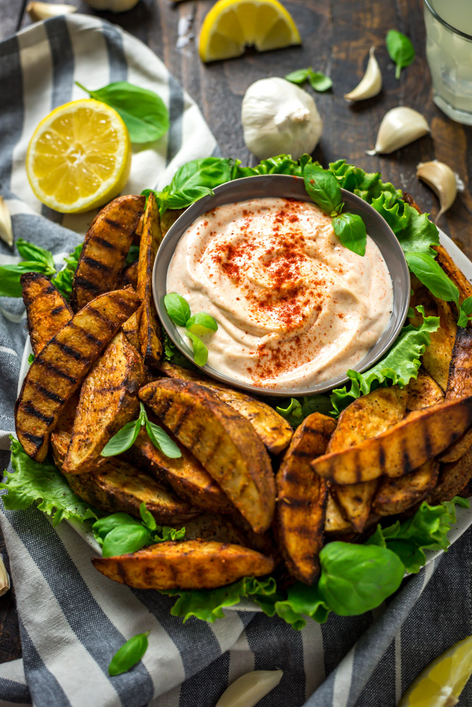 Grilled Potato Wedge Fries with Roasted Garlic Aioli. No burger is complete without a side of fries, so whip these easy grilled, seasoned wedges up for your next barbecue. The aioli, made from grill-roasted garlic, is just as addictive as the fries! | hostthetoast.com