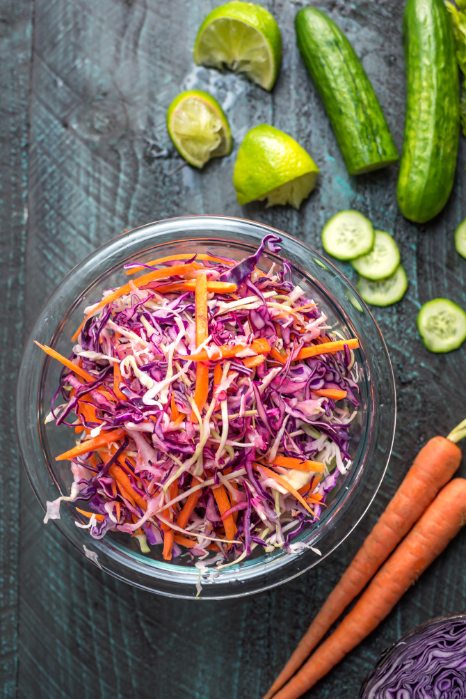Cabbage slaw for Korean-Inspired Crispy Tofu Tacos in a glass bowl on a blue wood table.