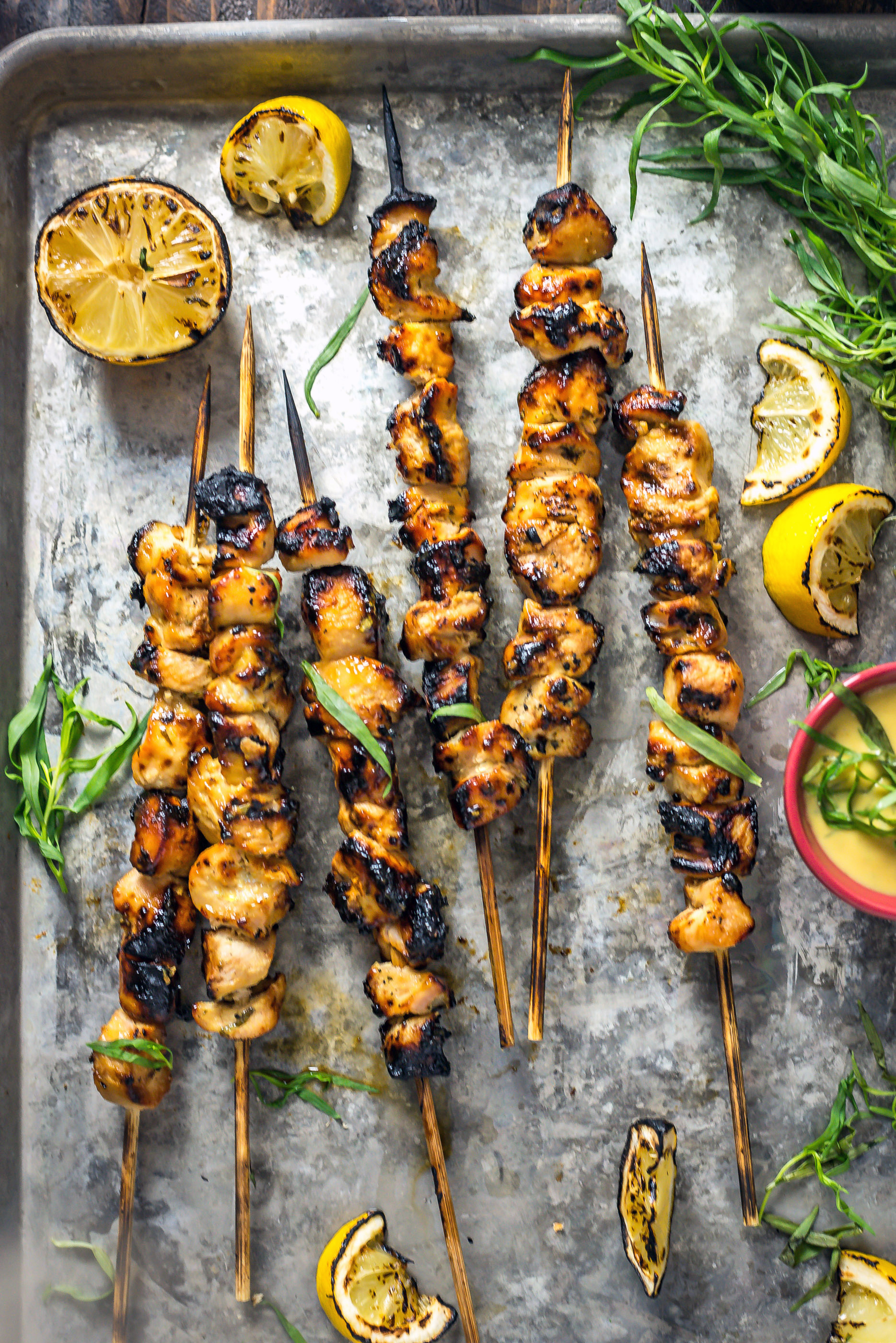 Grilled Tarragon Mustard Chicken Skewers on a baking sheet surrounded by grilled lemons.