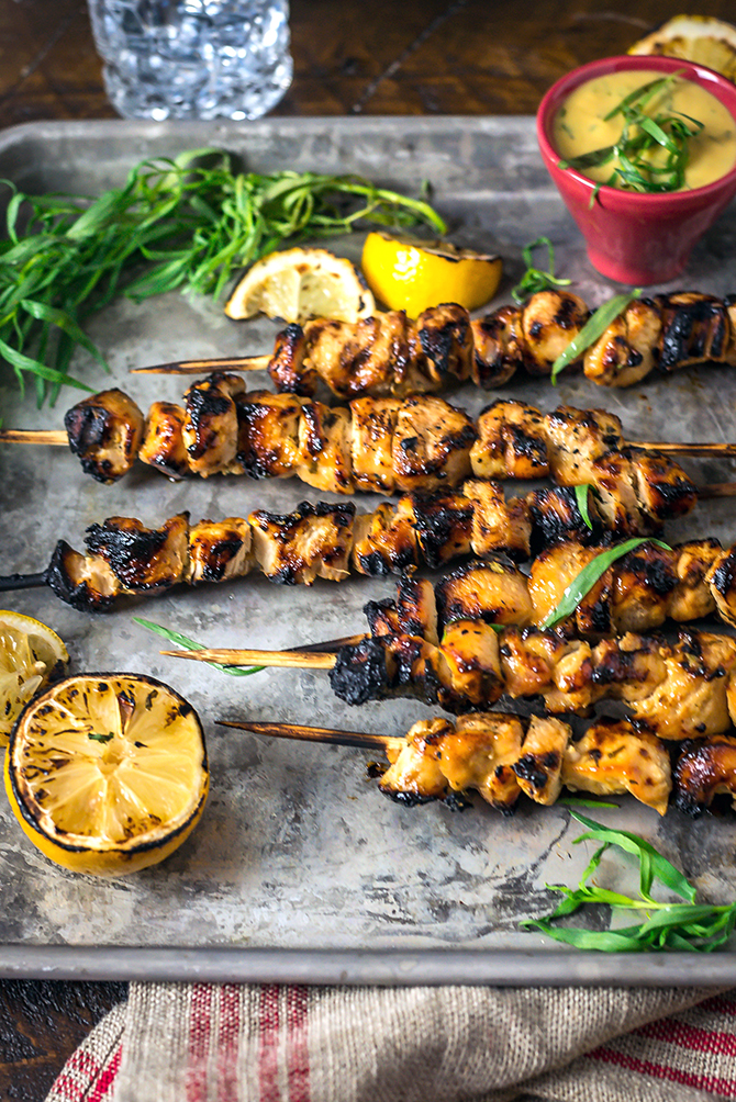 A side view of Tarragon Mustard Chicken Skewers set on a silver baking sheet.