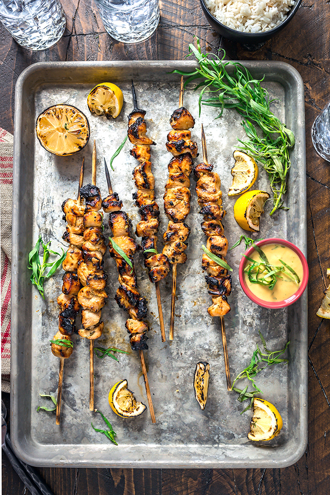 An overhead shot of Tarragon Mustard Chicken Skewers on a silver baking sheet.
