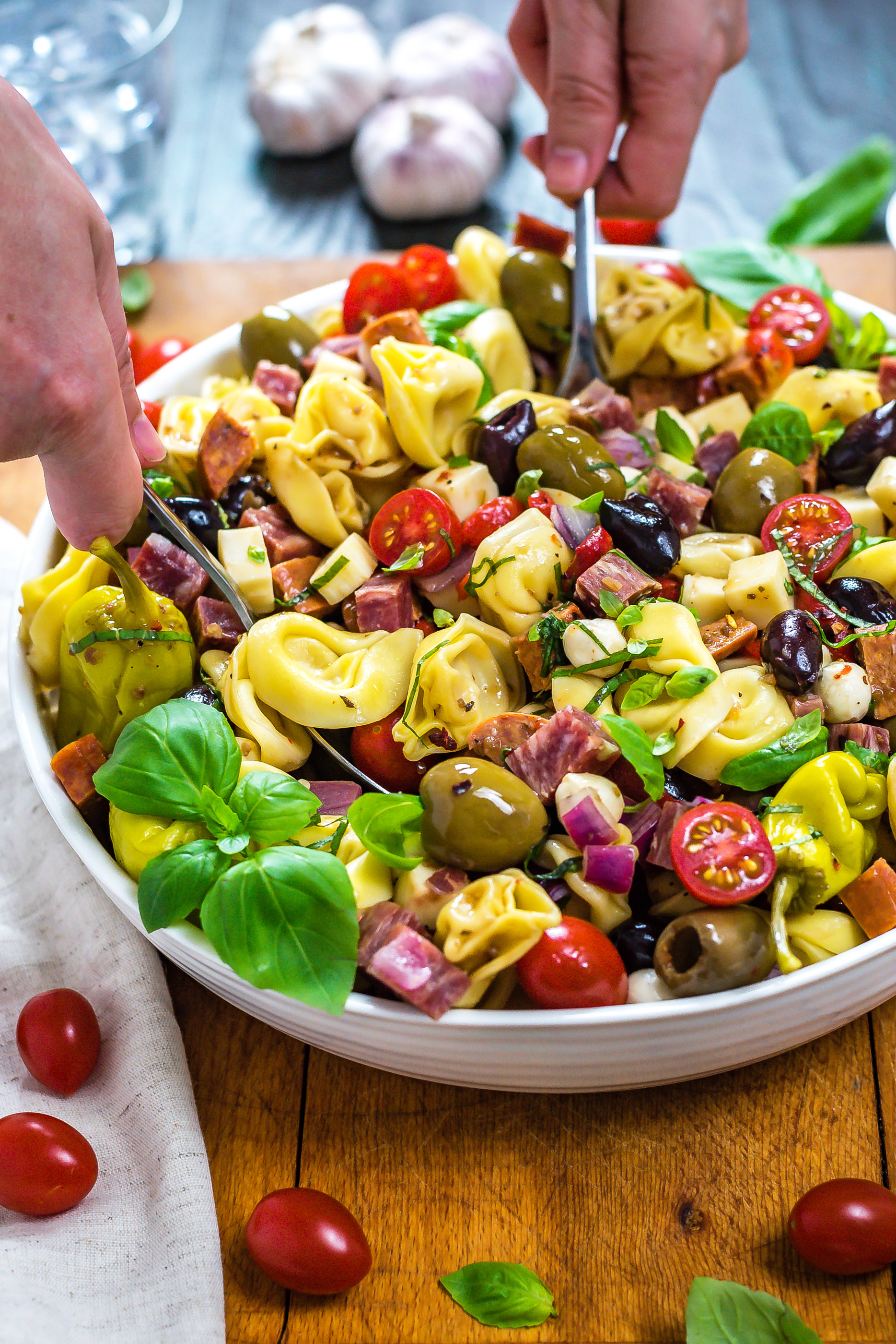 A side view of Antipasto Tortellini Pasta Salad being tossed together in a large bowl.