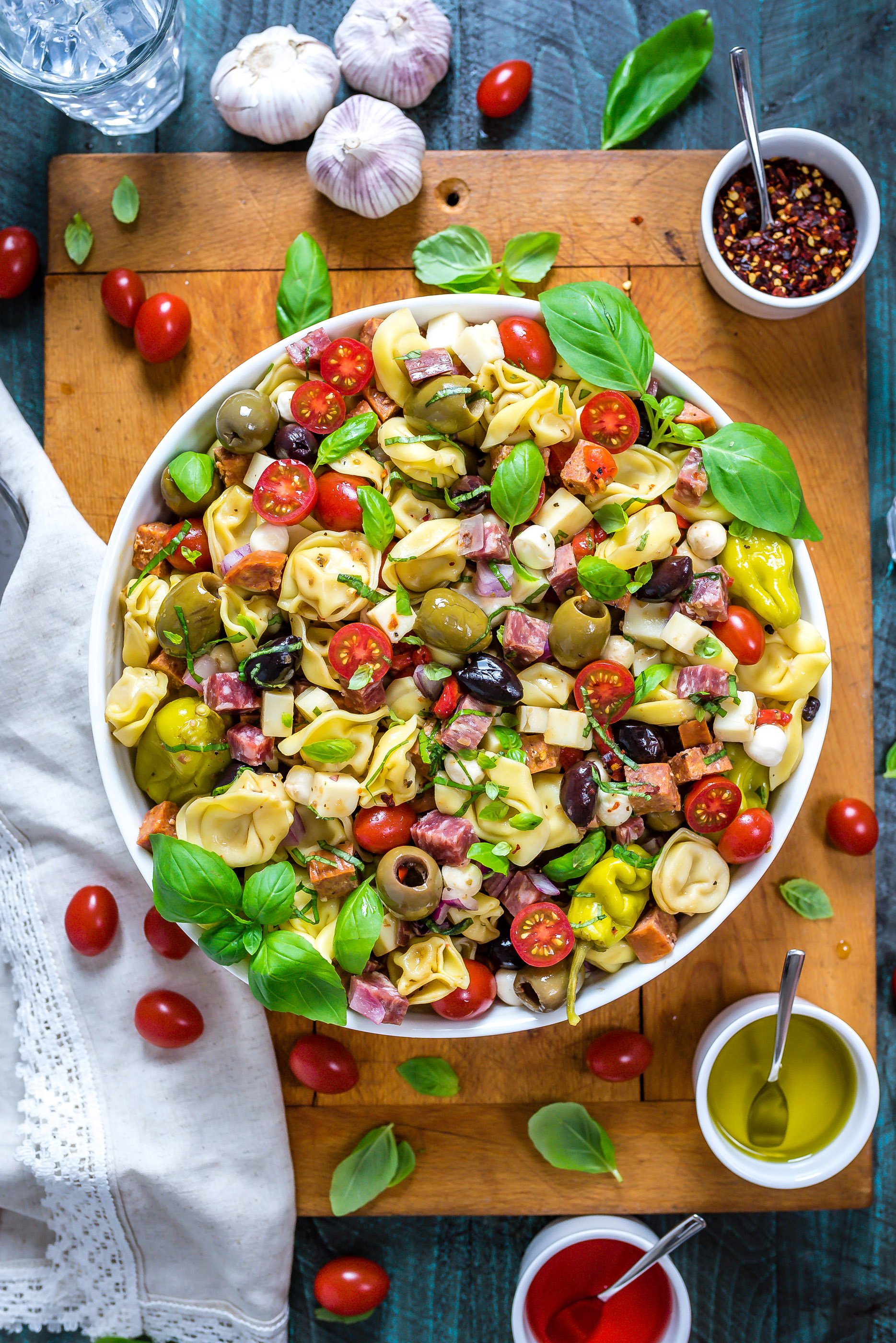 Antipasto Tortellini Pasta Salad in a large white bowl that rests on top of a wooden cutting board.