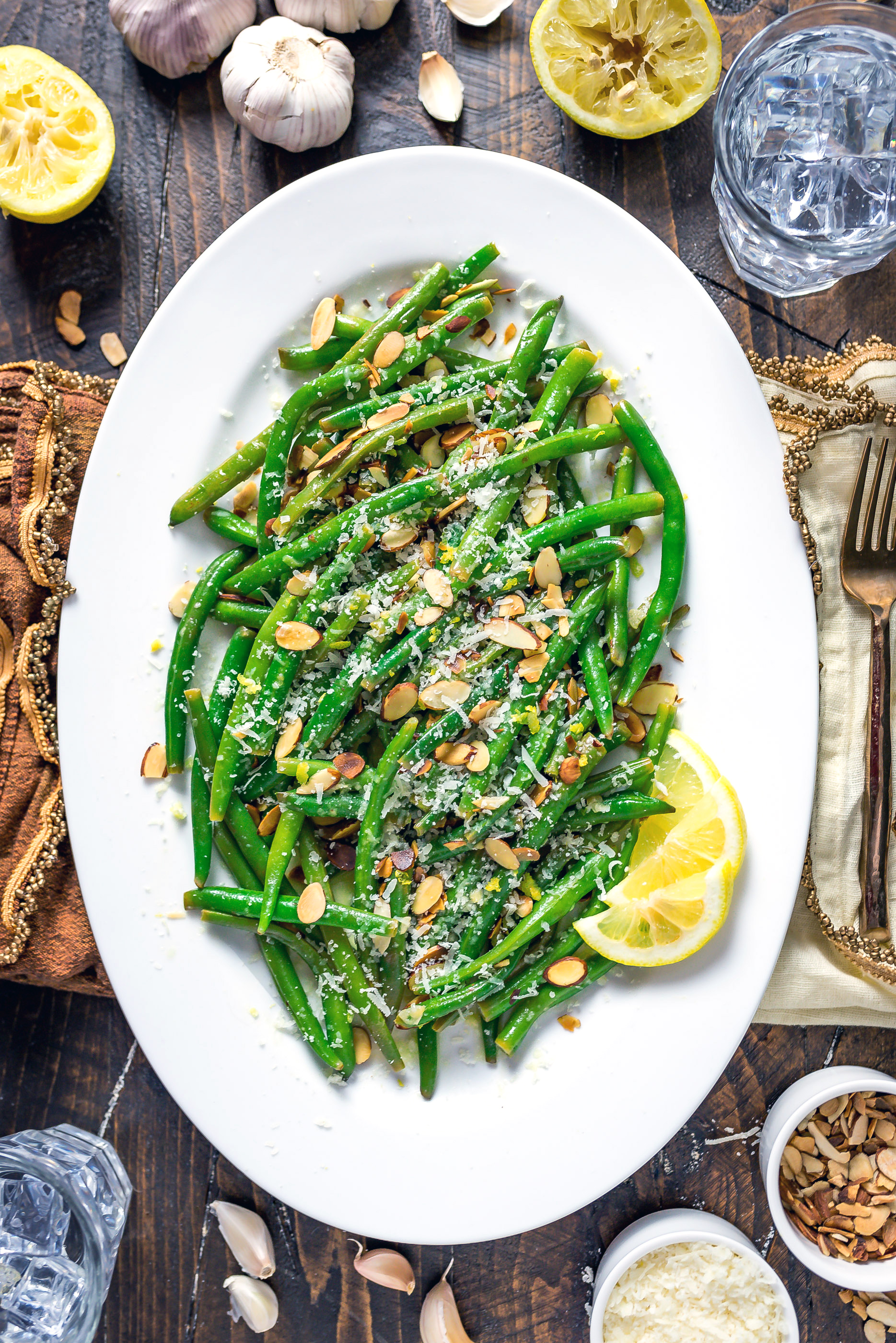 Browned Butter Lemon-Garlic Green Beans on a white plate with sliced lemon, almonds, and parmesan.