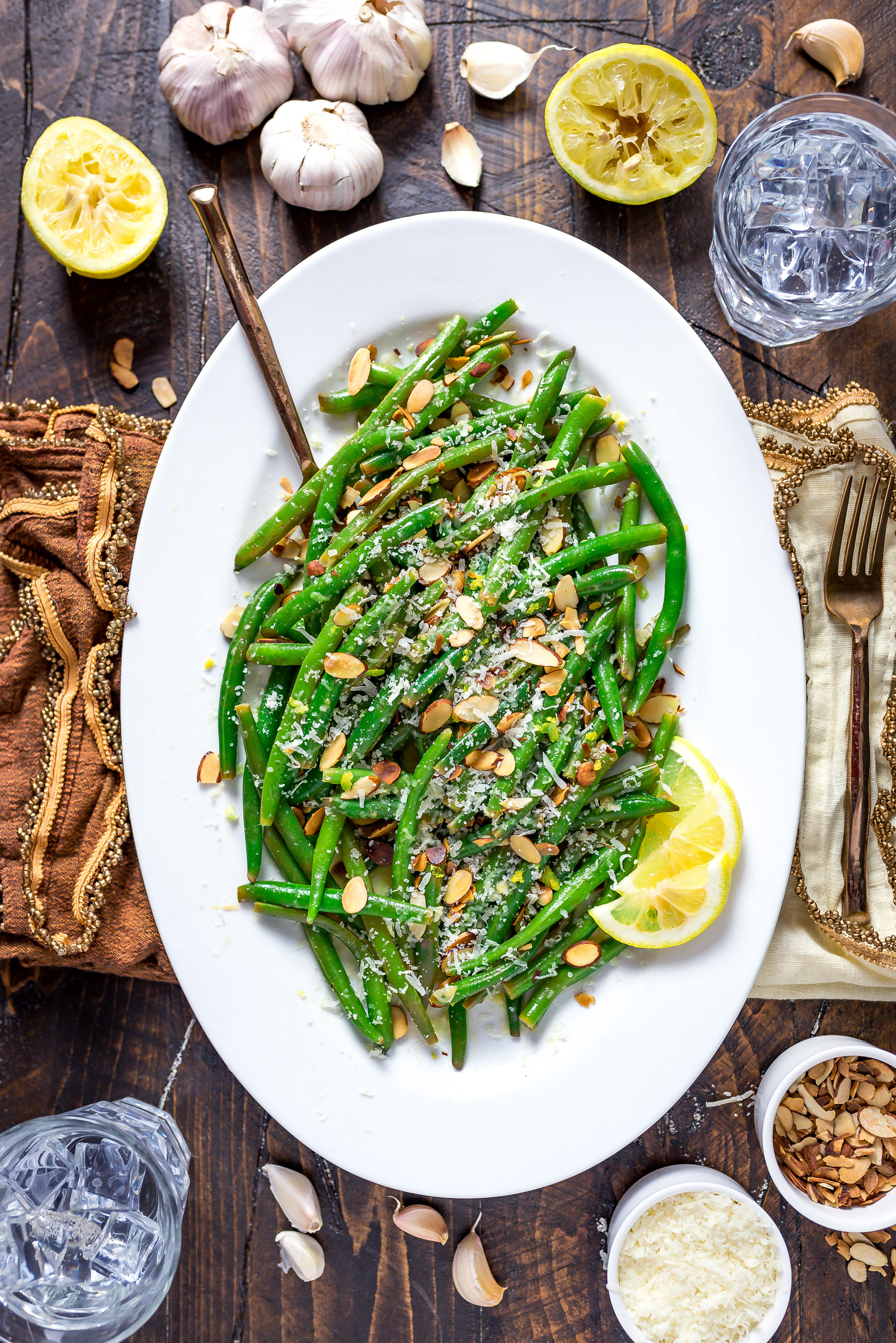 Browned Butter Lemon-Garlic Green Beans and lemon slices on a white oval-shaped plate.