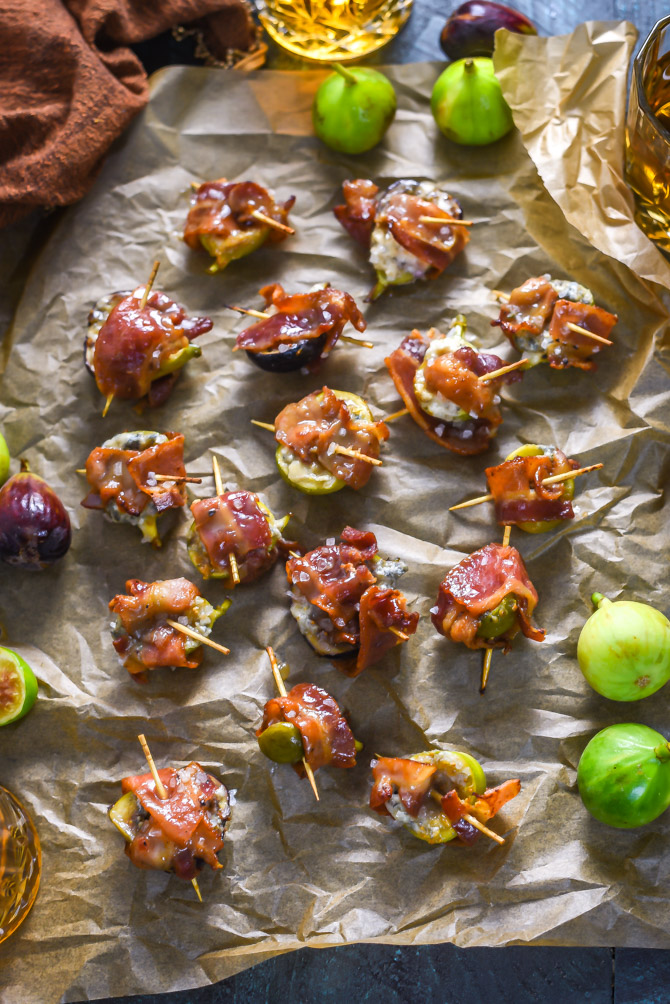 An overhead shot of Bacon-Wrapped Figs with Blue Cheese and Bourbon Caramel on a crumpled sheet of parchment paper.