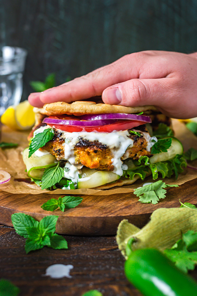 A hand pressing the naan bread down on top of Grilled Tandoori Chicken Patties with Jalapeno-Mint Yogurt Sauce.