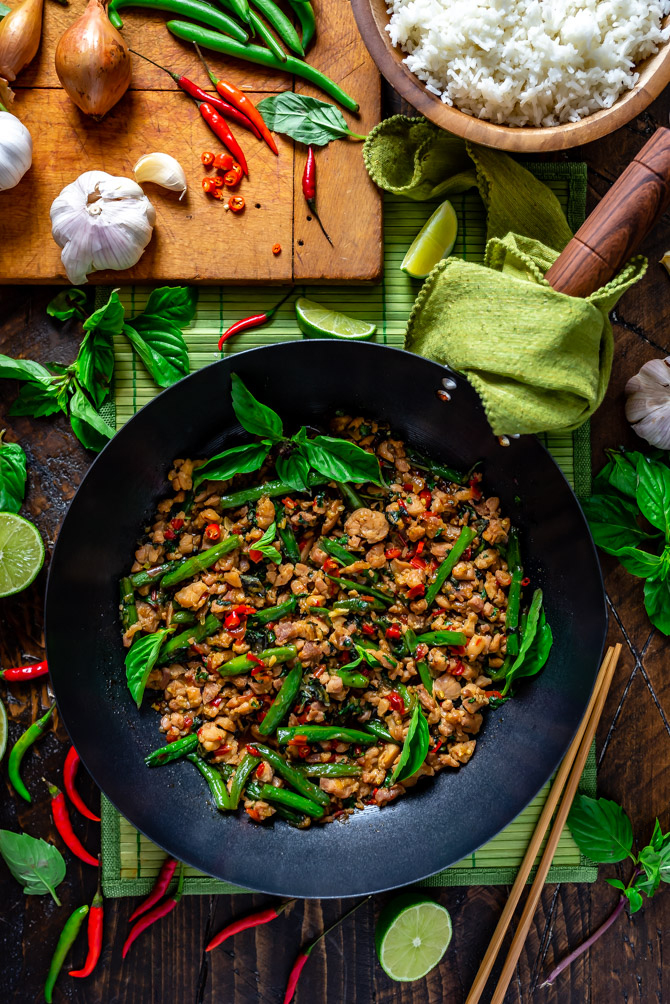 A zoomed out overhead view of 15 Minute Thai Basil Chicken in a wok surrounded by thai basil, limes, and thai chilies.