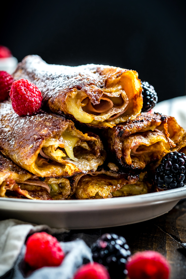 The classic sweet and savory sandwich gets transformed into the perfect rolled-up breakfast in the form of these Monte Cristo Crepes. Stuffed with ham, cheese, and a raspberry-dijon mixture, then dipped in egg and pan-fried in butter, they're as full of flavor as they are impressive when served for a brunch get-together. | hostthetoast.com