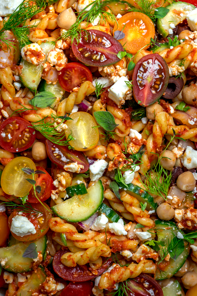 This super easy-to-make summer side dish beats store-bought pasta salad any day. Loaded up with Mediterranean flavors, Greek Pasta Salad with Sun Dried Tomato Vinaigrette is bright, zesty, and delightfully briney. | hostthetoast.com