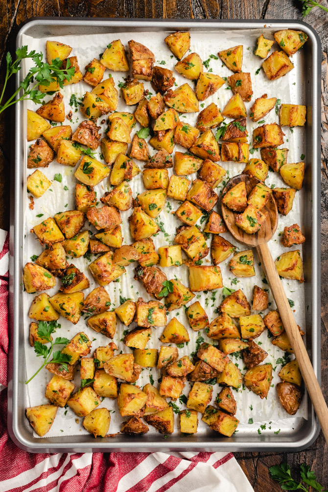 These easy-to-make Oven Roasted Red Potatoes are tossed with garlic, herbs, and parmesan cheese, and then baked until beautifully golden and crisp. Serve them as-is. or finish with butter and extra fresh parsley for a truly decadent and drooled-over side dish.