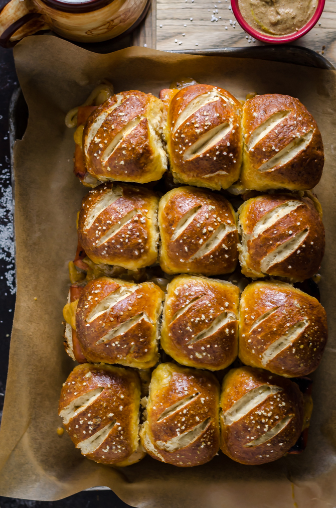 Bratwurst Sliders with Beer Cheese and Beer Braised Onions. These loaded sliders are served on pretzel buns and are perfect for parties or football season!   hostthetoast.com