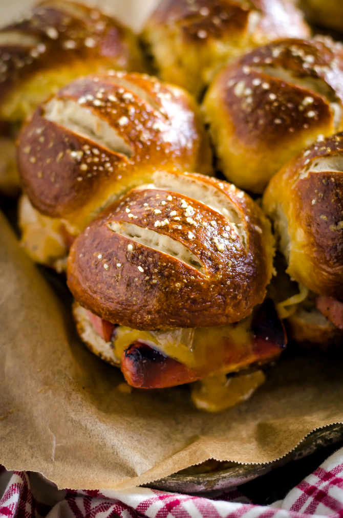 Bratwurst Sliders with Beer Cheese and Beer Braised Onions. These loaded sliders are served on pretzel buns and are perfect for parties or football season! | hostthetoast.com
