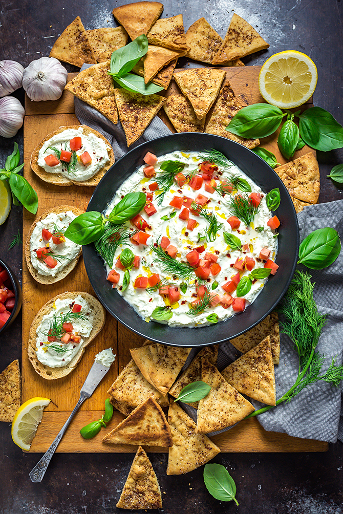Garlicky Feta Dip in a black bowl on a wooden cutting board surrounded by pita chips and bread.
