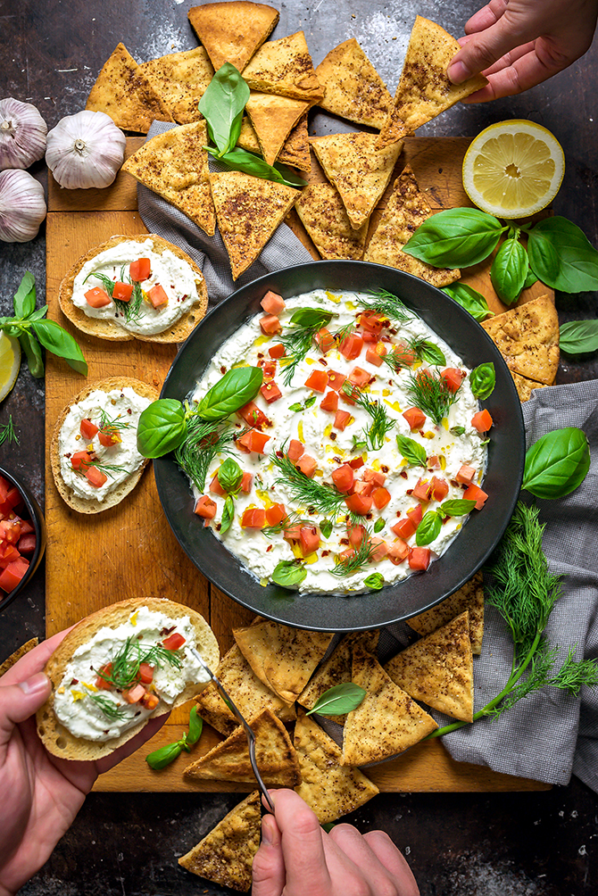 An overhead shot of Garlicky Feta Dip with hands grabbing the pita chips and bruschetta that surround it.
