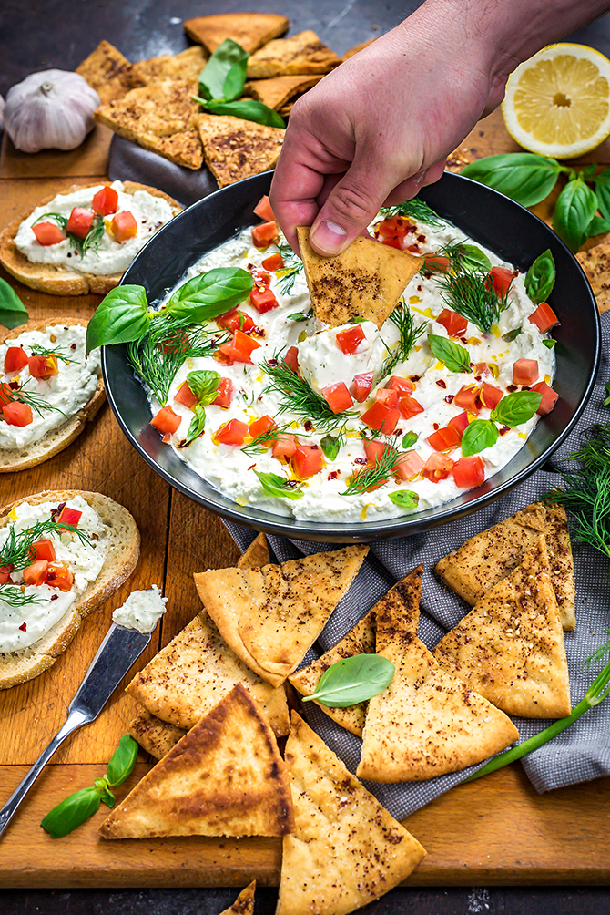 Dipping a pita chip into Garlicky Feta Dip in a black bowl.