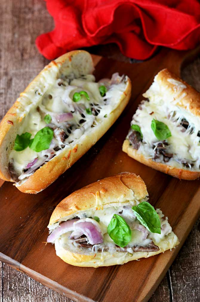 Ultimate Herbed Garlic Bread Cheesesteaks!  This delicious spin on the cheesesteak uses plenty of garlic, herbs and mozzarella!  You won't believe how good these are! | hostthetoast.com