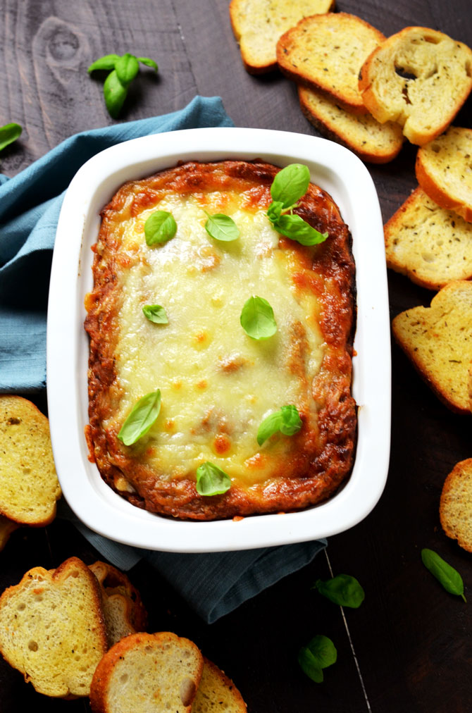Eggplant Parmesan Dip. This warm, cheesy dip is loaded up with tomato sauce, garlic, and roasted eggplant. I love making it for winter parties.   hostthetoast.com