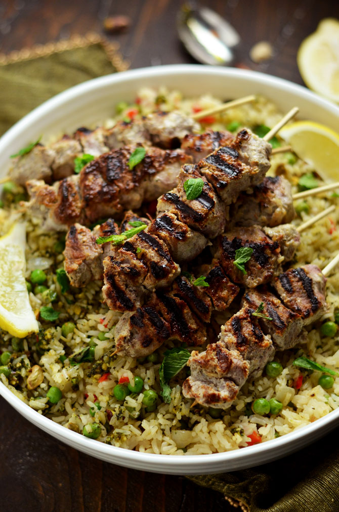 Yogurt Marinated Lamb Skewers with Mint Pistachio Pesto Pilaf. Marinating the lamb in a mixture of yogurt, garlic, lemon, and cumin makes it tender, tangy, and bright. The rice pilaf, with mint-pistachio pesto mixed in, is the perfect pairing for this springtime dinner.   hostthetoast.com