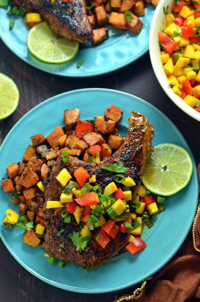 Jamaican Jerk Pork Chops with Curry Spiced Sweet Potatoes and Mango Salsa. A little heat, a little sweet, and a ton of Caribbean flavor combine in this simple dinner. | hostthetoast.com