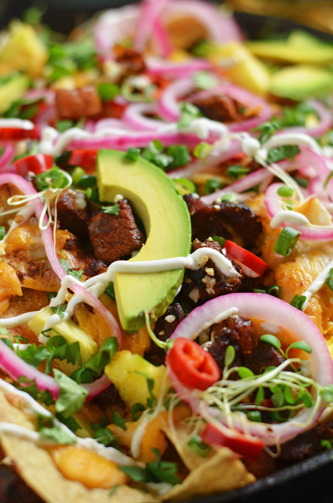 Nachos Al Pastor. These loaded nachos are piled with spicy, tangy pork, 3 kinds of cheese (including queso sauce), quick pickled onions and hot peppers, and more. This is how to do nachos the right way. | hostthetoast.com