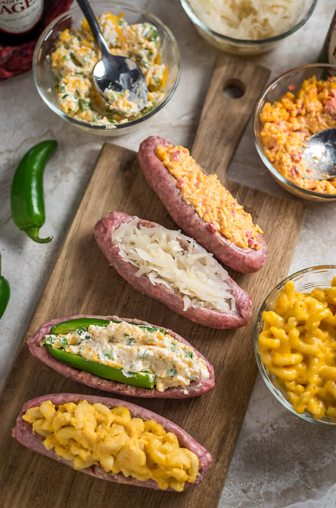 Bacon-Wrapped Stuffed Beer Bratwurst. Don't just put the toppings on your beer brats, put them *in* them, too! Stuff 'em, wrap 'em in bacon, and grill 'em until crisp. Click through for 4 filling ideas including mac & cheese, pimento cheese, sauerkraut, and jalapeño popper. | hostthetoast.com