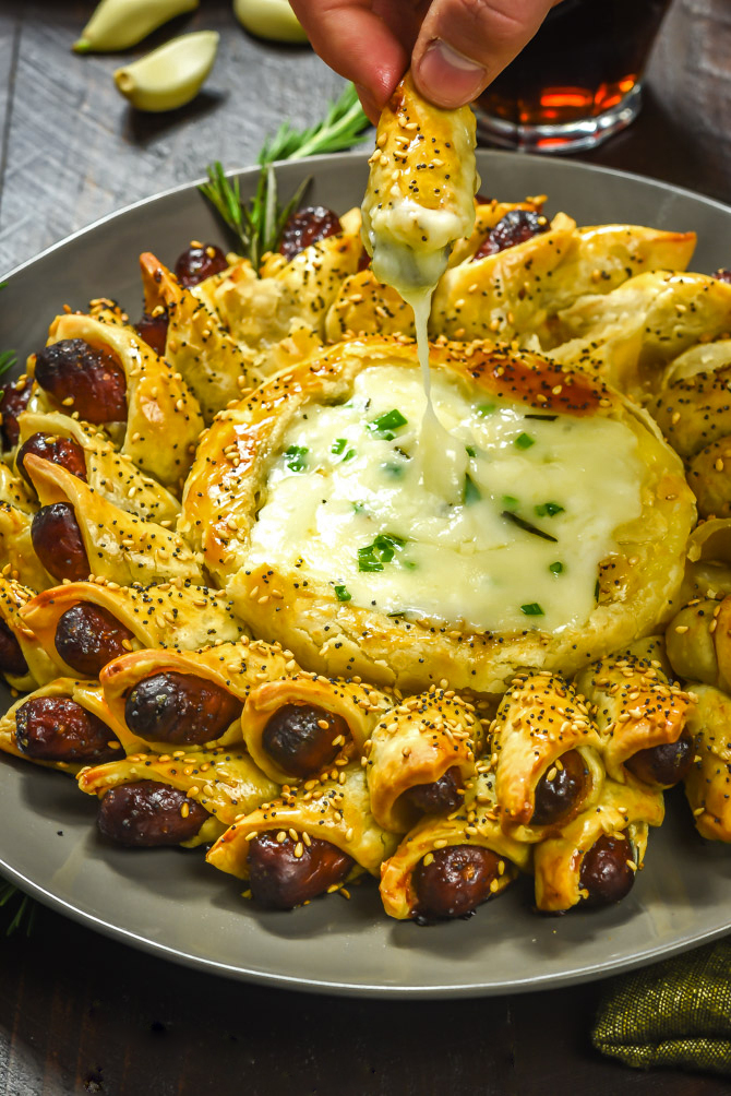 Pigs in a Blanket Baked Brie. This cheesy, garlicky, herby dip includes mini cocktail sausages in a premade pie crust! It's an easy and delicious party treat!| hostthetoast.com