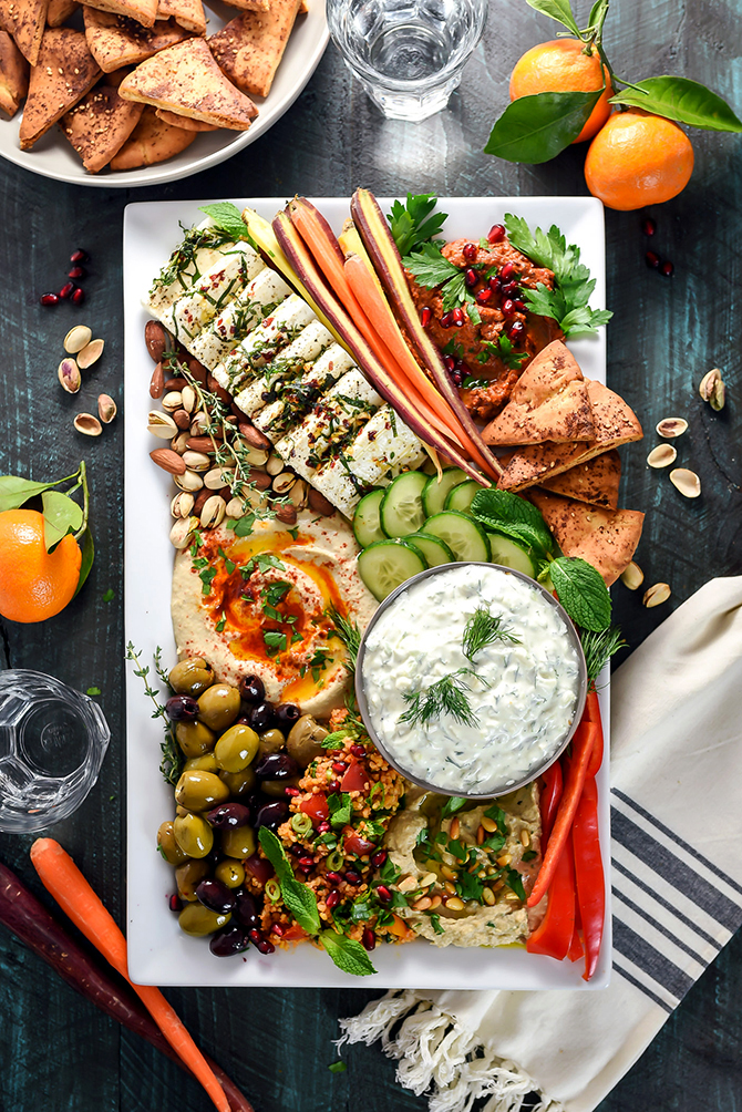 Mezze Party Platter. Loaded up with hummus, baba ganoush, marinated feta, tzatziki, tomato rice salad, muhammara, za'atar pita chips, sliced veggies, and nuts, this platter is the perfect spread of Mediterranean and Middle Eastern flavors. | hostthetoast.com