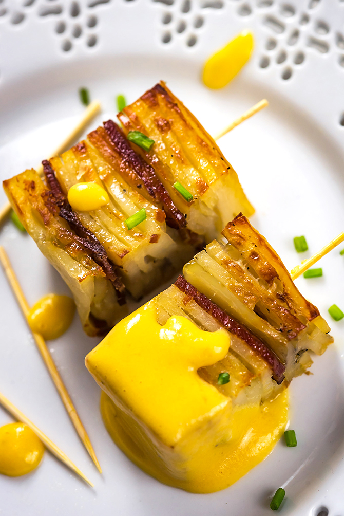 Party Potato Pave Bites with Cheese Sauce. Layered potatoes, bacon, and a creamy cheese sauce make this recipe a hit with a crowd! | hostthetoast.com