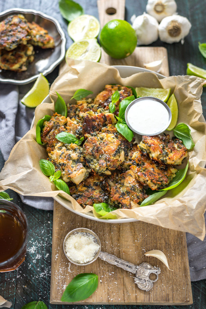 Spinach and artichoke dip fritters in a bowl that rests on top of a wooden cutting board.