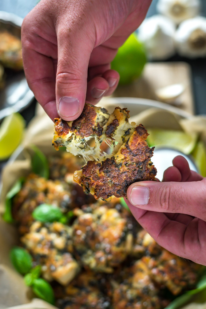 A spinach and artichoke dip chicken fritter is being pulled apart by two hands to show the cheesy insides.