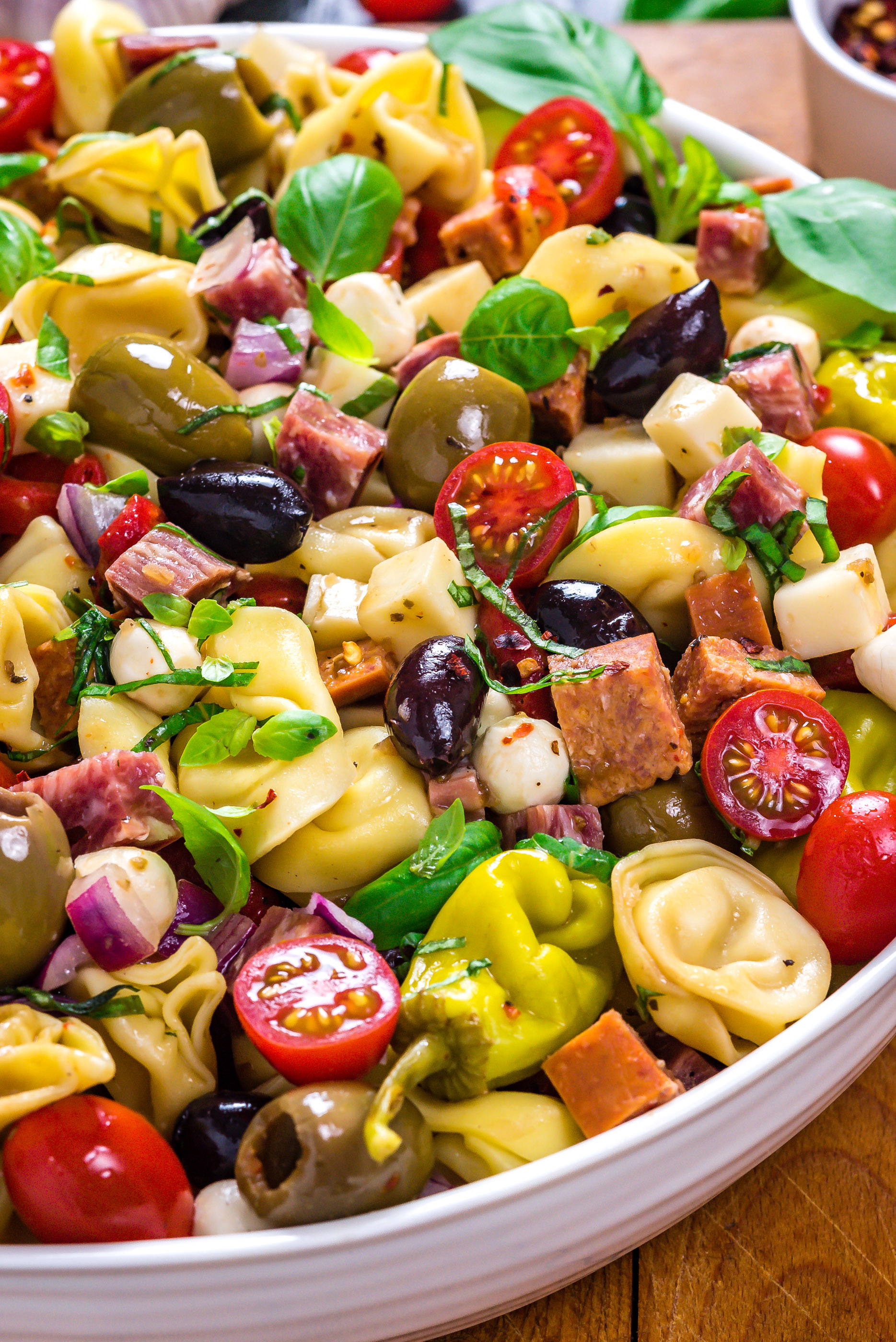 A close up side view of Antipasto Tortellini Pasta Salad in a large white bowl.