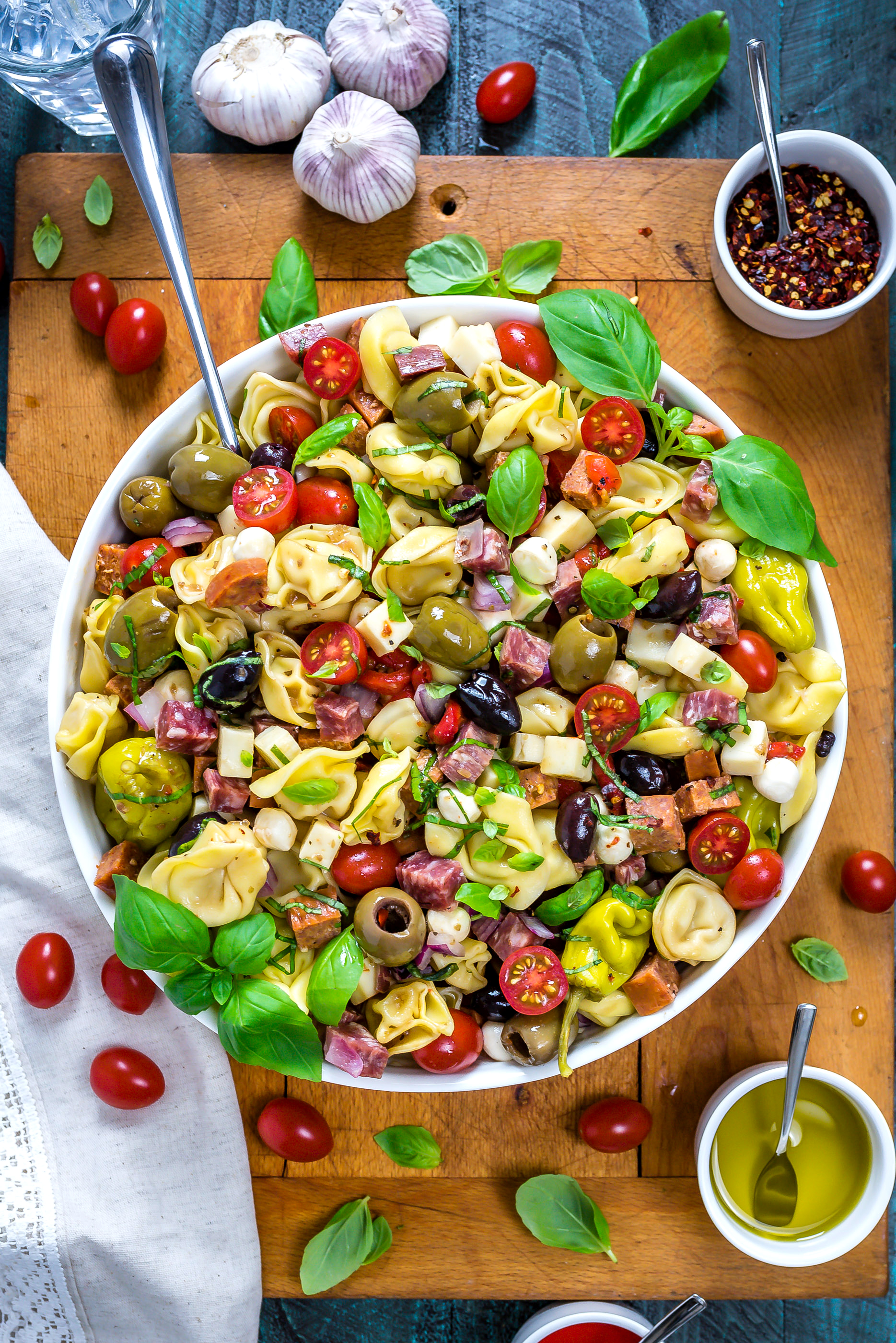 Overhead view of Antipasto Tortellini Pasta Salad in a large white bowl with a large serving spoon.