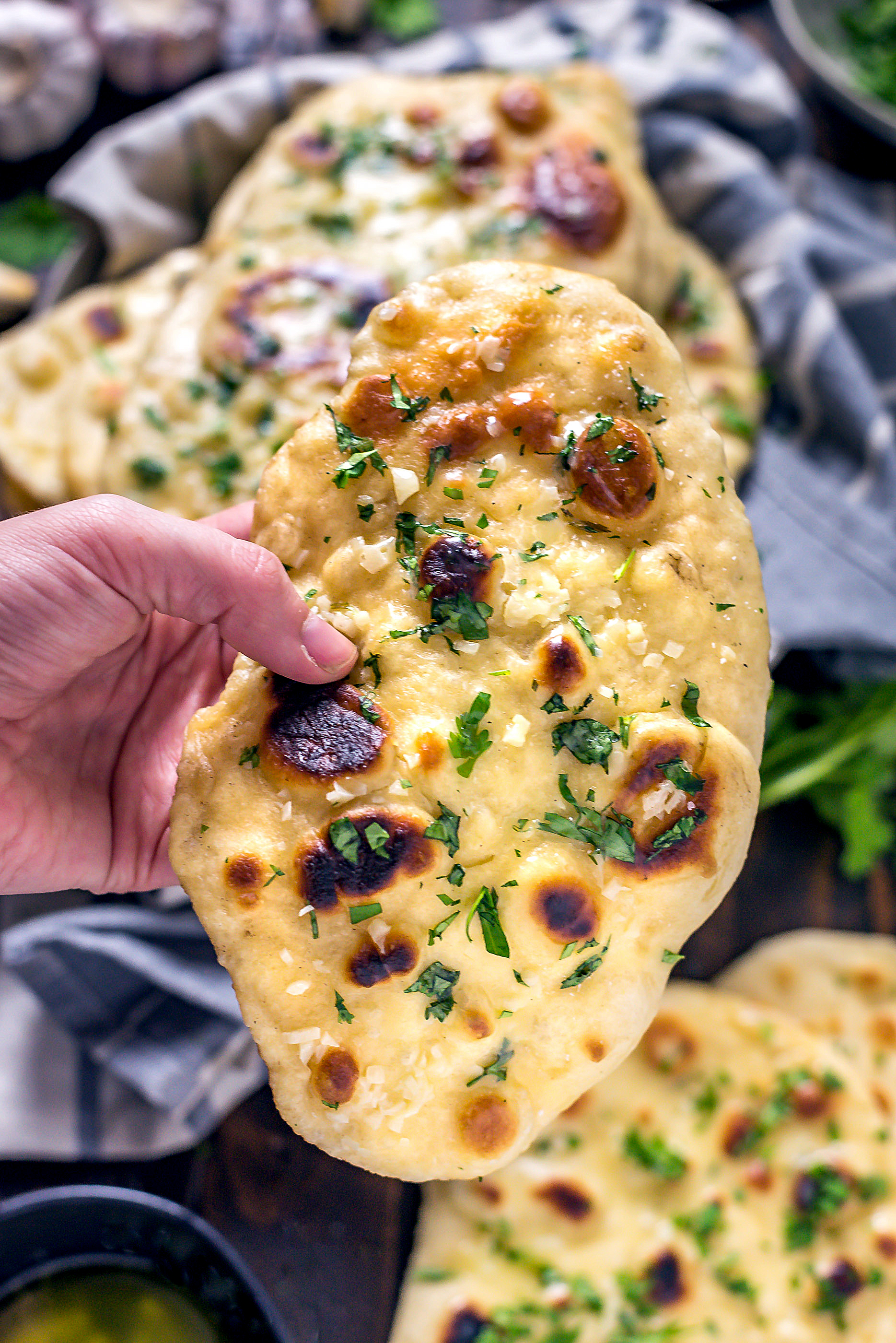 Hand holding up a soft piece of Homemade Garlic Naan.