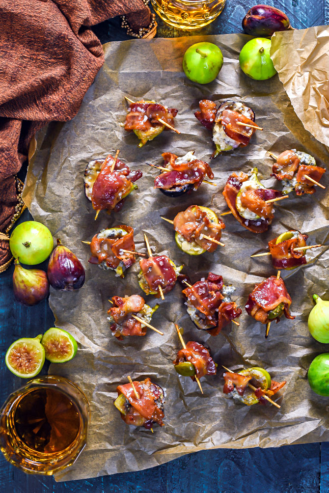 Bacon-Wrapped Figs with Blue Cheese and Bourbon Caramel on a crinkled sheet of parchment paper.