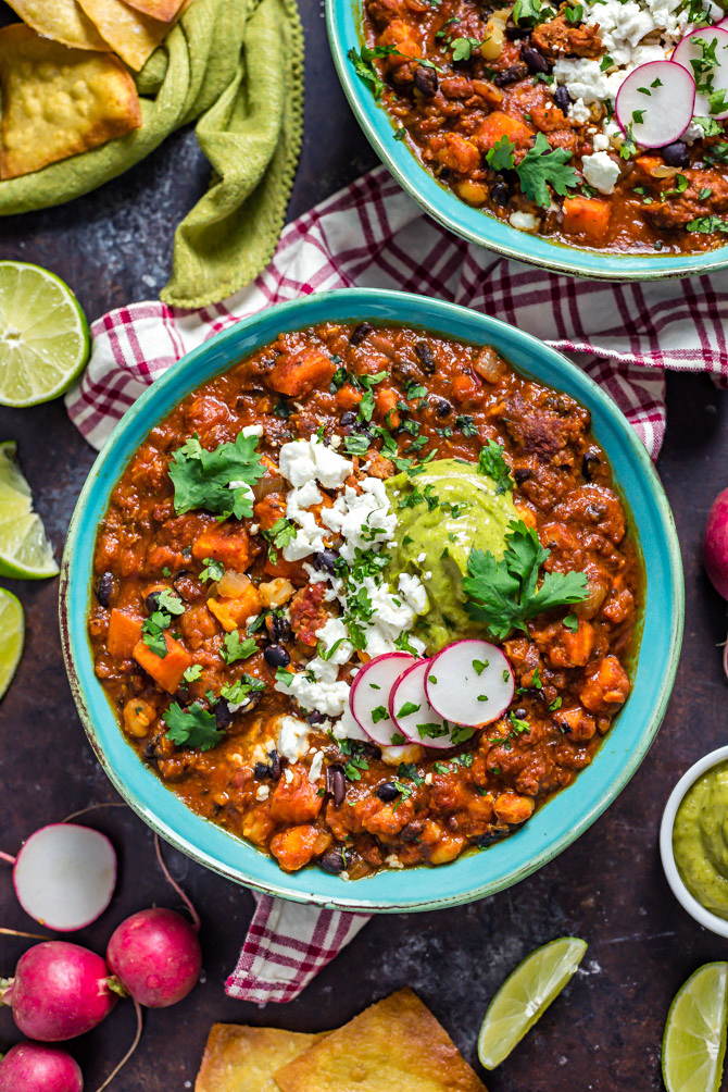 Two blue bowls filled with Sweet Potato Chorizo Chili, topped with bright green Poblano-Avocado Crema, goat cheese, sliced radishes, and cilantro.
