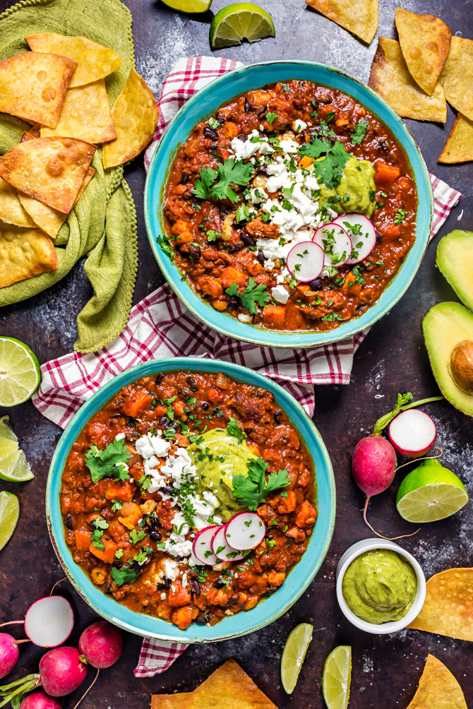 Overhead shot of two blue bowls filled with Sweet Potato Chorizo Chili, surrounded by tortilla chips, limes, and radishes.