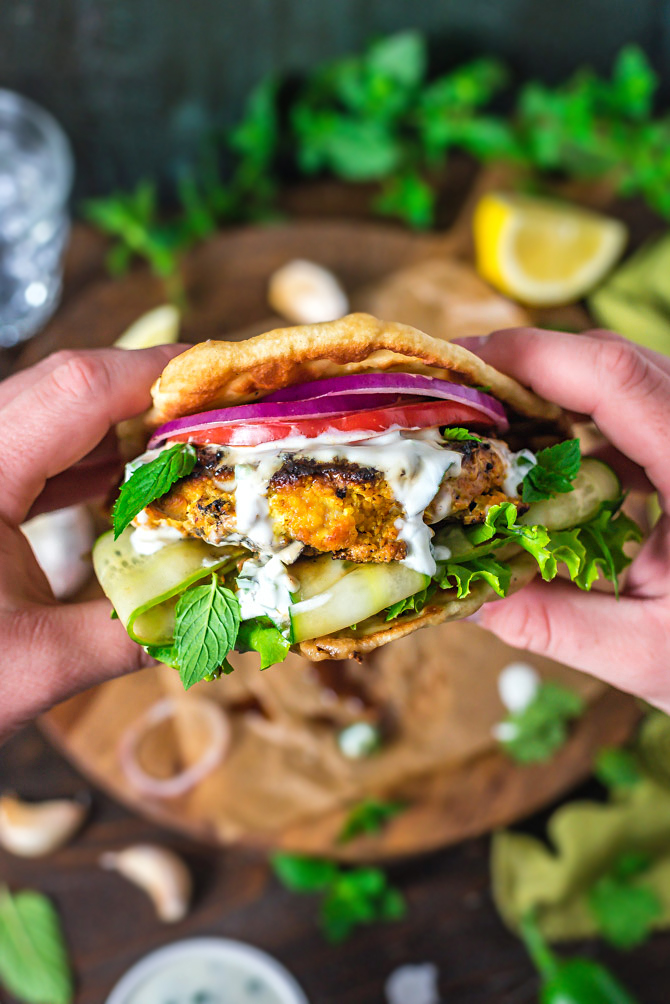 Two hands holding up a Grilled Tandoori Chicken Patty with Jalapeno-Mint Yogurt Sauce.