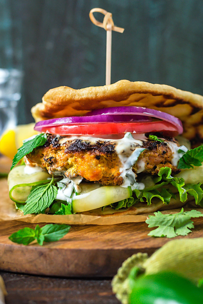 A close up side view of Grilled Tandoori Chicken Patties with Jalapeno-Mint Yogurt Sauce.